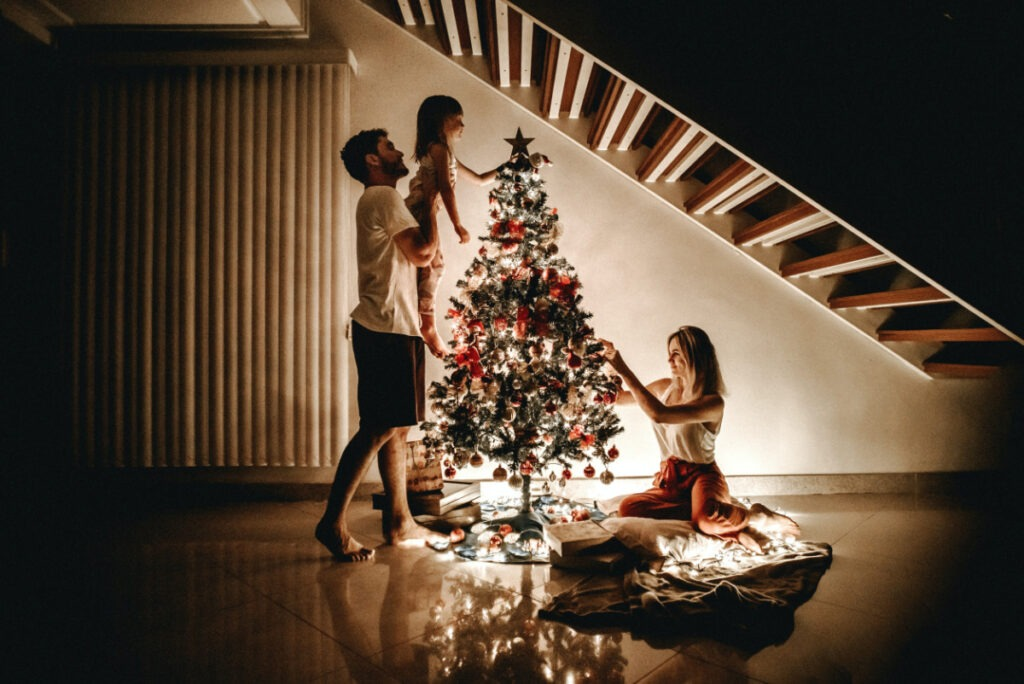 small family decorating christmas tree during covid-19