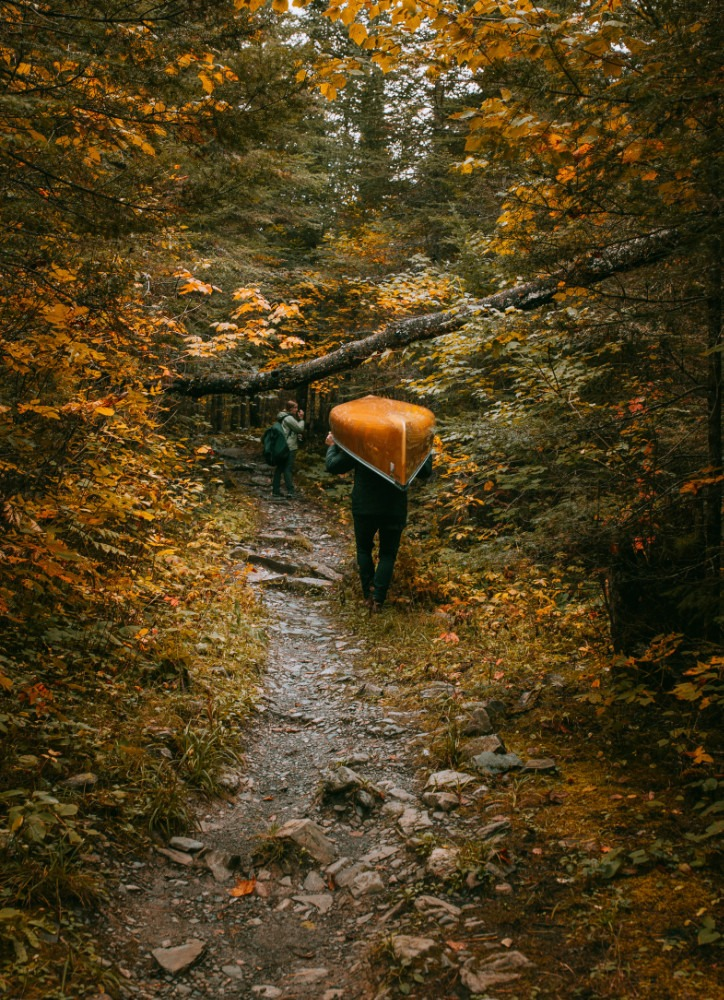 person carrying canoe over head on trail through the woods in the boundary waters