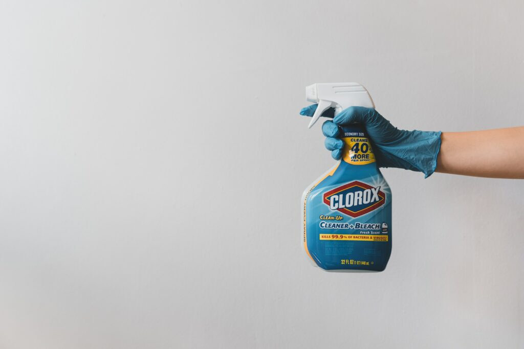 arm with blue rubber glove holding clorox spray bottle for spring cleaning